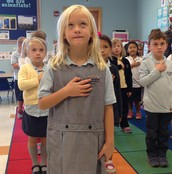 Avery leads  the Pledge of Allegiance.