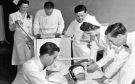 Doctors and Nurses preparing to treat a patient with electroconvulsive shock therapy.