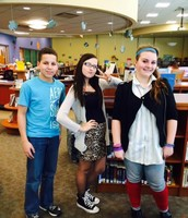 Middle School students dressed in retro attire pose for a photo