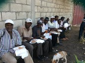 Hard working farmers are rewarded with a meal after helping prepare compost