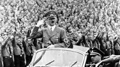 Hitler riding in his car greeting the people.