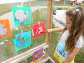 Mila painting animals onto the easel