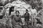 Ojibwe People infront of wigwam