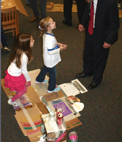 Lily and Natalia show Board President Mr. Van Hise How to Play