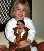 Girl holding a doll of Adolf Hitler