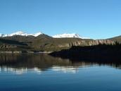 Hay montañas y bosques alrededor del lago
