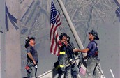 Firefighters holding up flag in the rubble