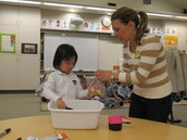 A Parent Helper Oversees the Measuring of Trail Mix Snacks!