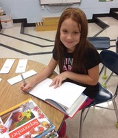 A 2nd Grade Media Assistant processing new books.
