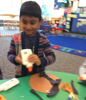 Rithik follows the directions as he puts a dot of glue on the paper