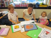 Olaf looks at his colourful work with his mummy and sister