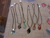 These lovely blown-glass pendants are strung on leather tongs by Carol van Tol.