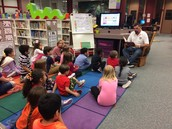 Fathers reading to children in the library