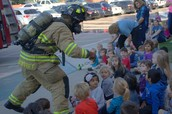 Firefighter showing the kids not to be scared of fire equipment