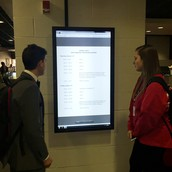 Learners utilizing touch screen for schedule updates.