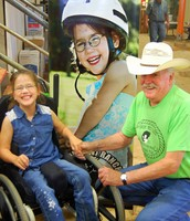 Ranch Rider, Kaylee, and her favorite volunteer, Mr. Jay, with the Ranch banner featuring her picture.