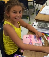 Emma works on her Social Studies Goods & Services Poster
