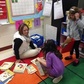 Mrs. Letourneau and students sorting books.