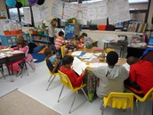 Shelly Breitbeil getting up from the small group reading table to check on kids doing their independent work