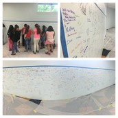 Our Pillow students & staff sign a wall in the new library where bookshelves will go!