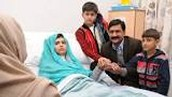 Malala in the hospital with her brothers and dad.