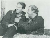 A picture of Lennie and George sitting on a hay stack.