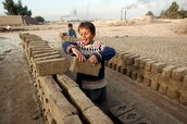 A young child stacking bricks.
