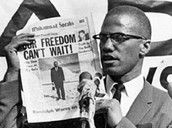 Malcolm X Holds Up an Article For His Cause