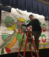 Mr. C hangs backdrop he created for the Cinco de Mayo celebration!