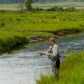 A man fishing in a nearby river
