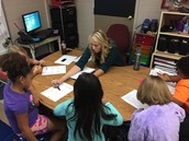 Miss Blair working with a small group of reading students.
