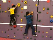 Children working hard to make it through the rock wall during PE.