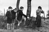 Three boys picking on another little boy becasue he isn't wearing the same clothes they wear.