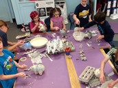 Students creating paper mâché piggy banks.