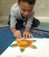 Zyir using his imagination with pattern blocks.