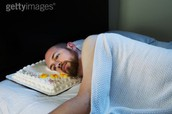 A sad man laying down on a cake