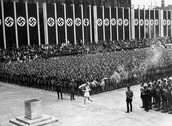 Image of the Olympic torch being carried with the Nazi flags in the background