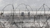 Prisoners walk along the fence of North Korea's Camp No. 9