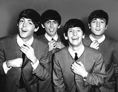 All the Beatles  smiling for a picture.