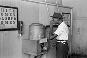This is a picture of a a black  man drinking out of a different water fountain then white people!