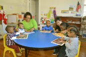 This is a child care worker and her assistant reading to the children