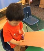 Darren is very focused to make his community helper book