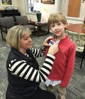 Mom putting on Principal Mauldin's name tag