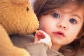 A kid plays with a teddy bear