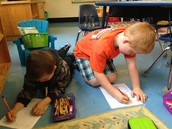 Daniel and Sam help each other spell words.