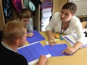 Mrs. Newell conferences with her 2nd grade students about their Performance Series data.