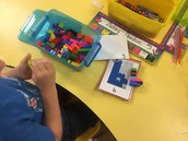 Using our fine motor skills to build letters out of legos.