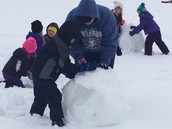 ALC students help Kindergarten students build snowmen