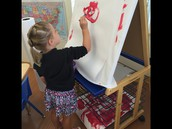 "Delaney painting ""red"" at the easel!"