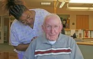 An old man talking with a nurse